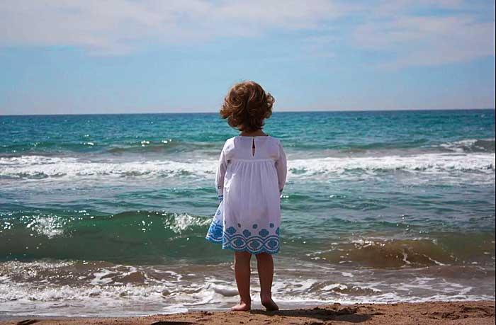 Niña contemplando el mar, reflejo de la belleza del Creador